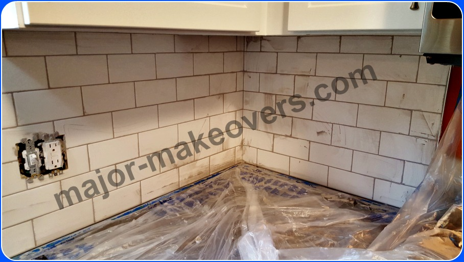 Probably the messiest part of a kitchen backsplash is grouting the tile but that's no problem when your countertops, stove, etc. are protected by taped plastic sheets.