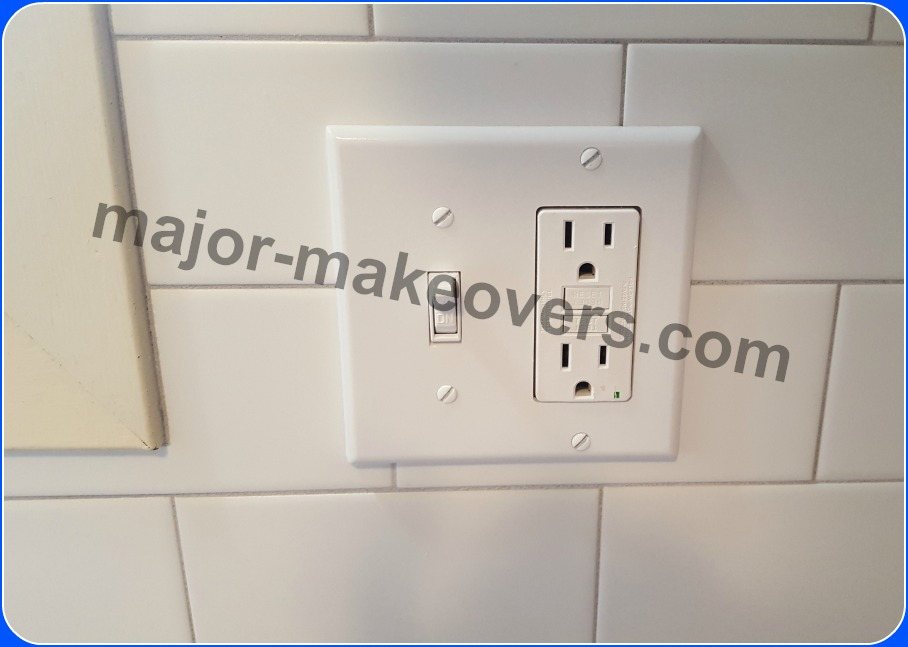 Plastic cover installed over switch and outlet on new backsplash tile. No problem plugging in a properly installed outlet with tabs on tile. Grout is stain resistant Whisper Grey from The Tile Shop.