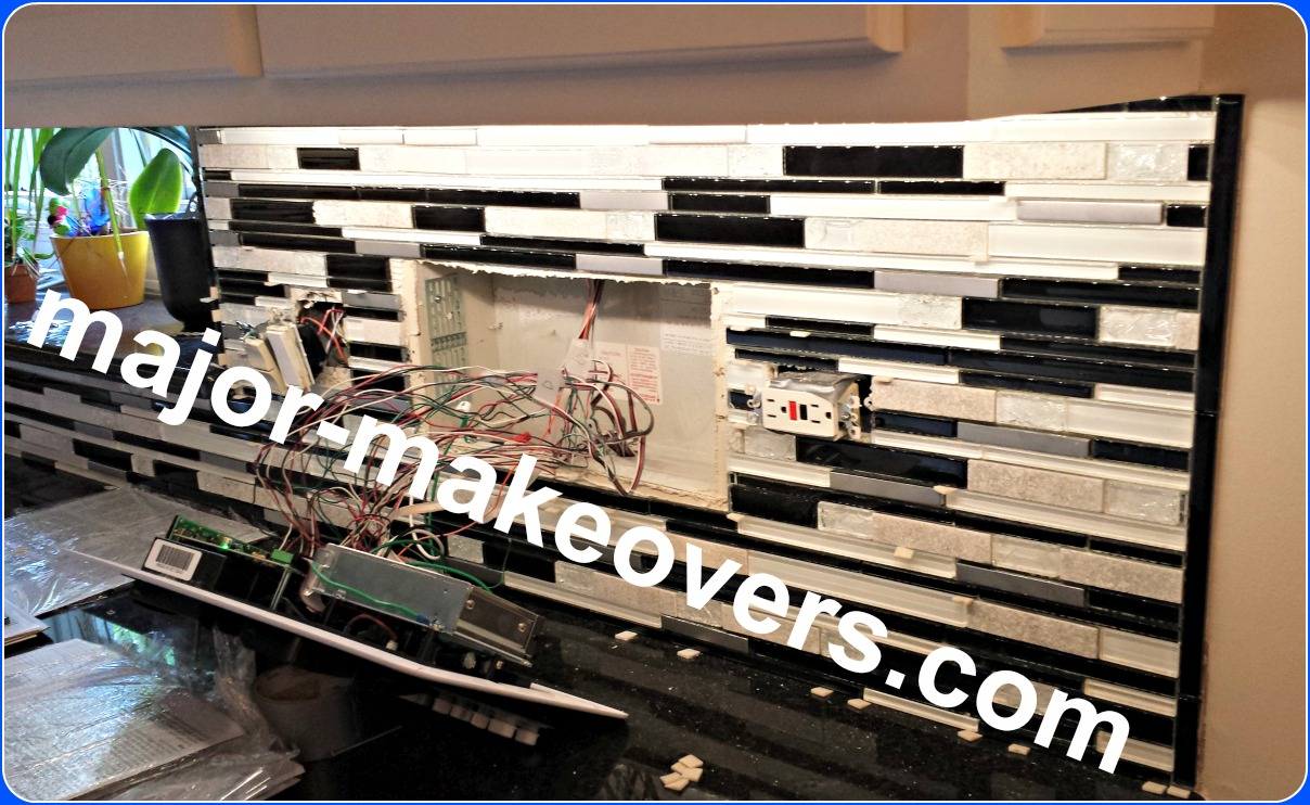 Tile installation around electrical switches, outlets and intercom panel with lots of wires. Black glass strips make the edge of backsplash. #BestHinsdaleTileInstallers #TileInstallationHinsdale60521