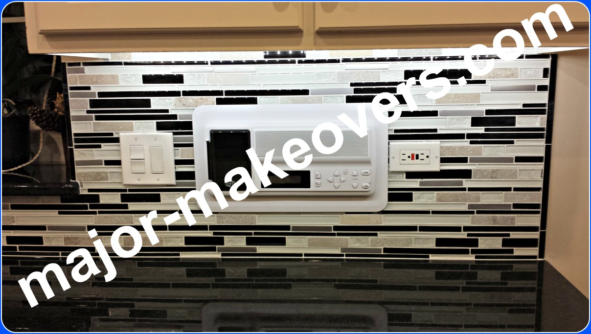 Big intercom panel installed between switches and outlets on the bright backsplash tile. Vertical trim starts on window sill - trim seen on the right side too. #TileInstallersHinsdale #DiscountTile