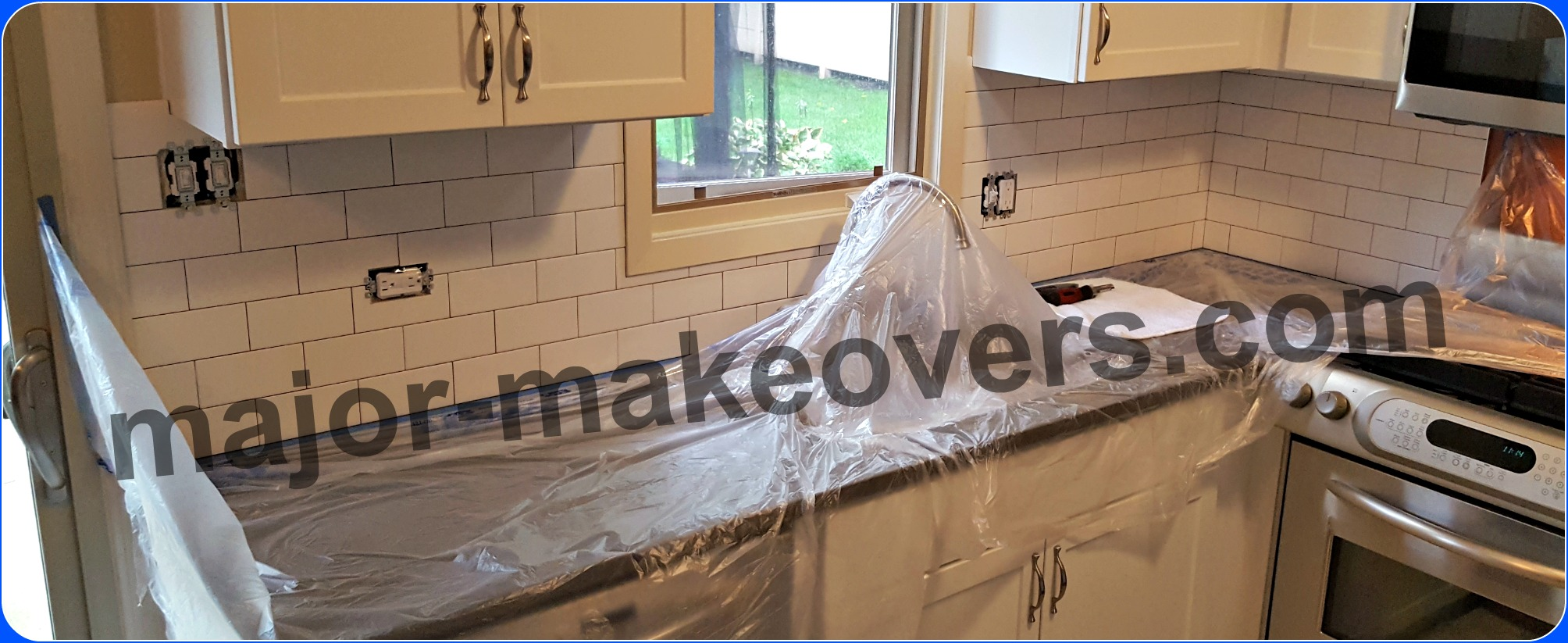 Backsplash tile ready for grouting while countertop, faucet and stove are protected by taped plastic sheets. Duct tape or similar, is placed on all switches and outlets.