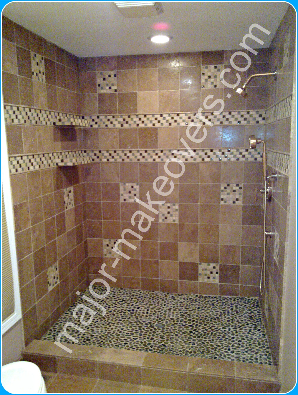 Sealed travertine tile installed on shower walls with 2 decorative mosaic and pencil tile lines - round pebble tile on shower floor and two 6x18 in. custom shower dishes/shelves.