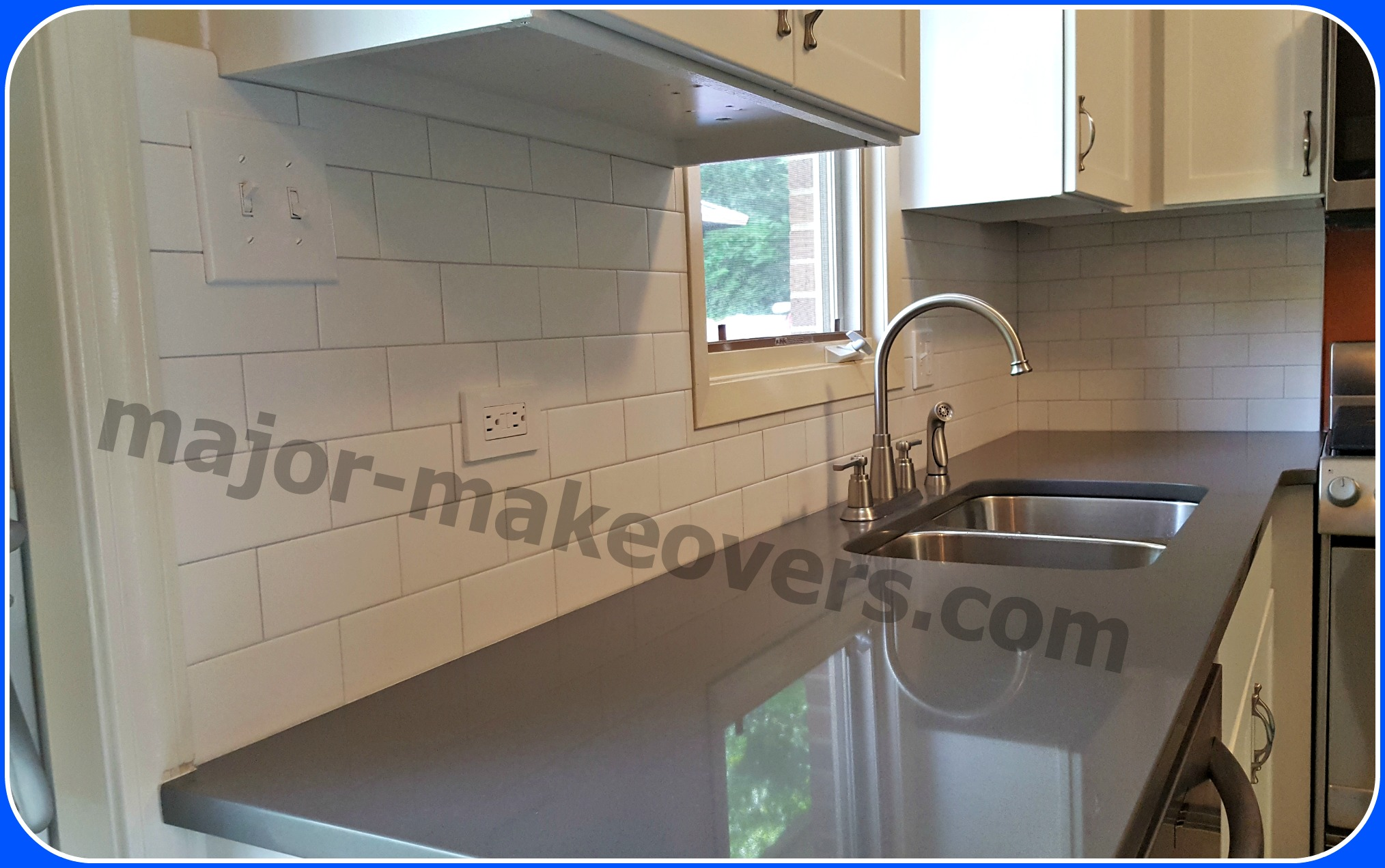 Complete backsplash tile installation. White cabinets and tiles are combined with dark grey countertops. Stainless steel appliances go with metal tile trims and cabinet door knobs and drawer handles.