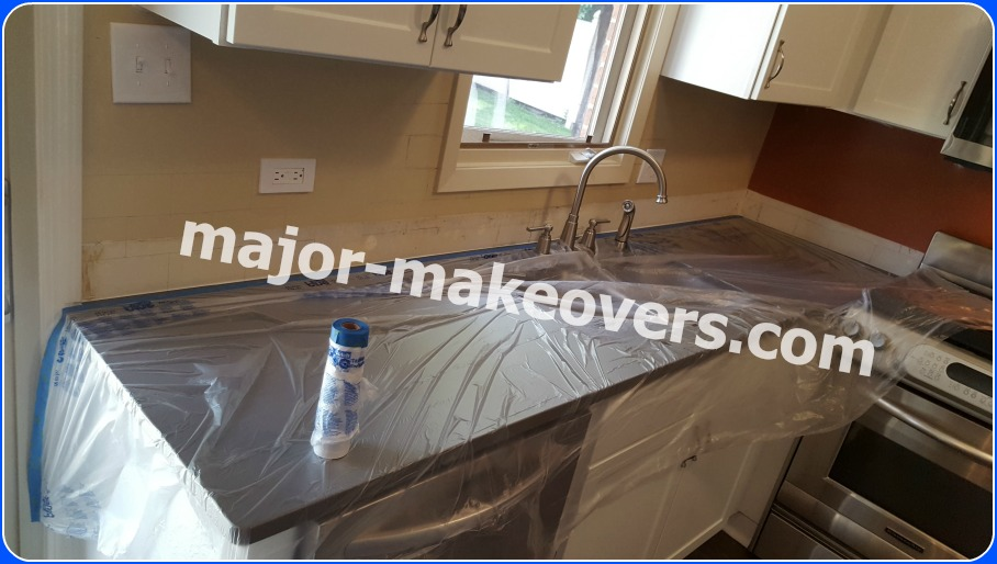 Plastic sheets being taped to protect countertops and stove during backsplash tile installation and grouting.