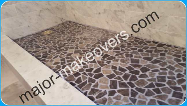Shower floor made of stones that were on mesh but had to be peeled away and installed as separate pieces to ensure room for grout and avoid water damage.