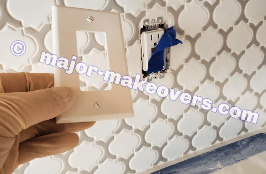 After grouting is done, tape is removed to install covers for outlets and switches within the backsplash area.