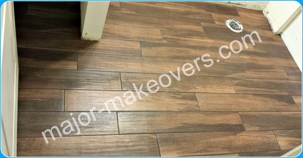 Apartment bathroom floor tile installation. The wood look porcelain tile is 6 x 36 inch and brown in color with black grout.