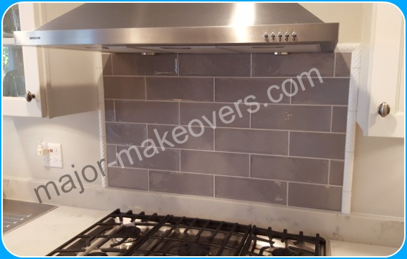 Very small grey backsplash tile with border/frame decorative tile to cover the edges. Backsplash tile just for the above the cooktop area.