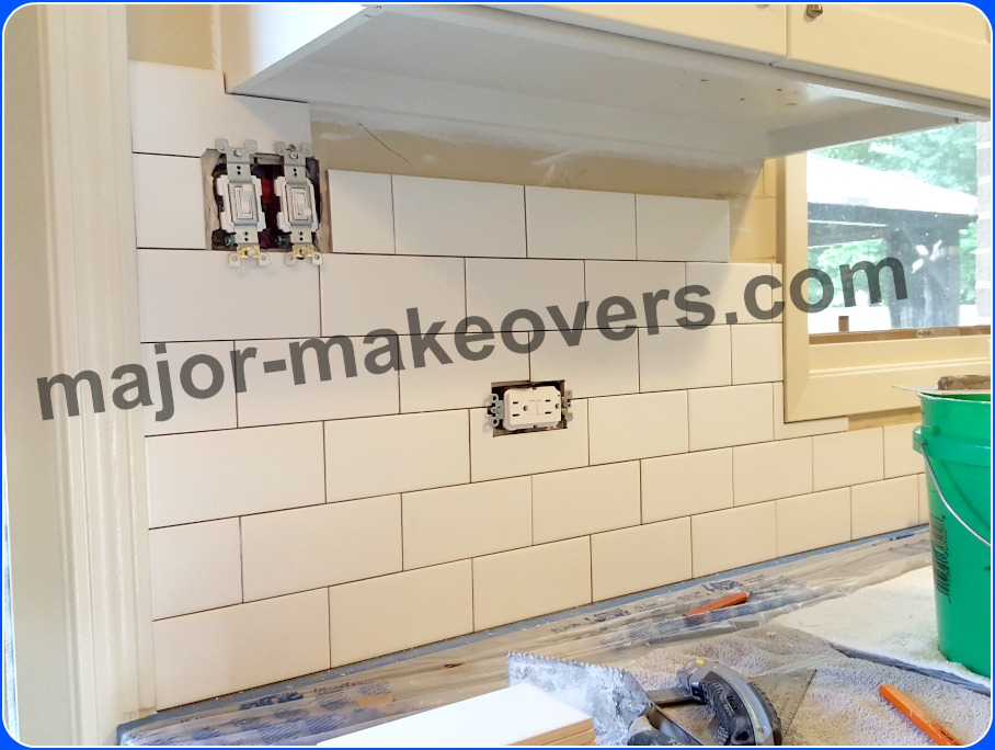 Kitchen backsplash subway tile installation in progress while countertops are protected with taped plastic sheets and towels over plastic. Tile size is 3 by 6 in. installed in a brick style/pattern.