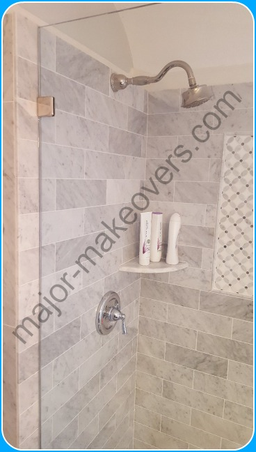 4x12 brick style marble installed on shower walls and 4 ft. high surrounding bath walls. Corner soap dish, mosaic wall insert and glass shower panel in view.